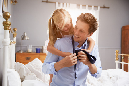 getting together: Daughter Helping Father To Get Dressed For Work