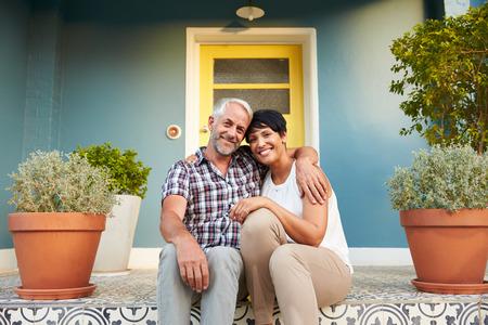 pareja en casa: Pareja madura Sentado en pasos fuera de la casa Foto de archivo