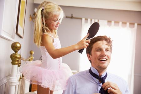 딸이 머리를 빗 으면서 일할 준비를하는 데 도움이되는 아버지 스톡 콘텐츠