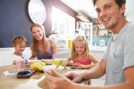 가족은 아침 식사 테이블에 디지털 장치 사용