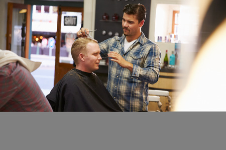 hairdressers shop: Male Barber Giving Client Haircut In Shop