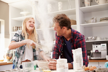 Father and daughter making a cake together photo