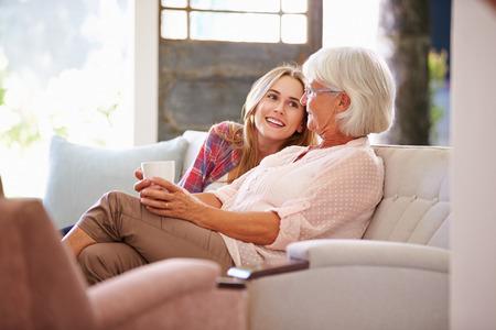 personas hablando: Abuela con la nieta Adulto relaja en el sofá
