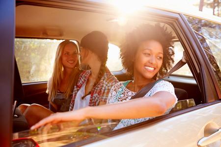 mujeres felices: Tres mujeres sentado en el asiento trasero del coche en viajes por carretera