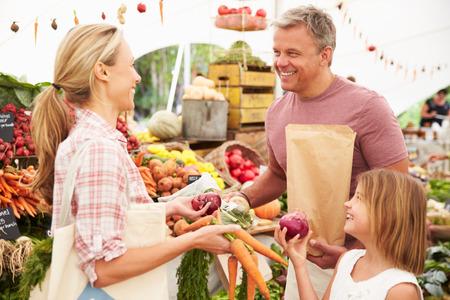 家族農民市場の屋台で新鮮な野菜を購入