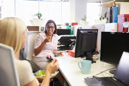 personas comiendo: Dos mujeres que comen el almuerzo en el trabajo
