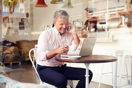 hombre tomando cafe: Hombre de mediana edad sentado en un caf� Foto de archivo