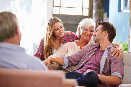 Familie met volwassen kinderen ontspannen op de bank thuis samen