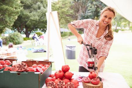 juicing: Woman Juicing Fresh Pomegranates At Farmers Market Stall Stock Photo