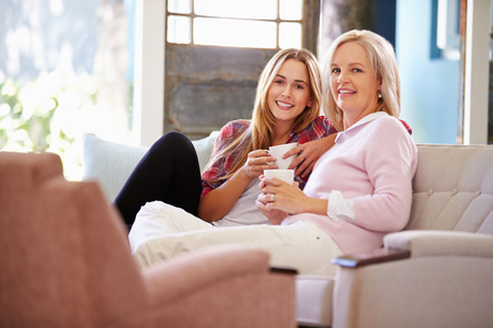 tea hot drink: Mature Mother With Adult Daughter Relaxing On Sofa At Home