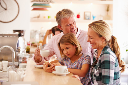 concentrating: Happy family in a cafe