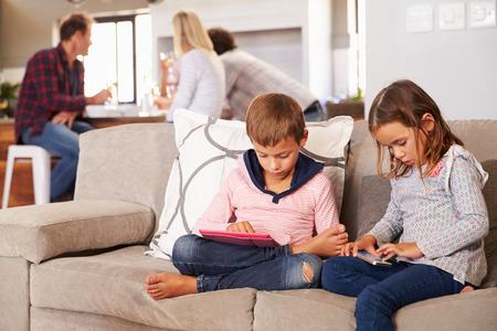 enfant qui joue: Enfants jouant avec les nouvelles technologies tandis que les adultes divertir