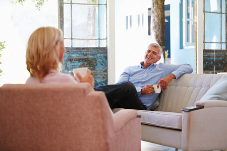 Mature Couple At Home Relaxing In Lounge With Hot Drink photo