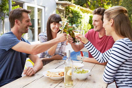 verano: Grupo de amigos que disfrutan de bebidas al aire libre en el jard�n