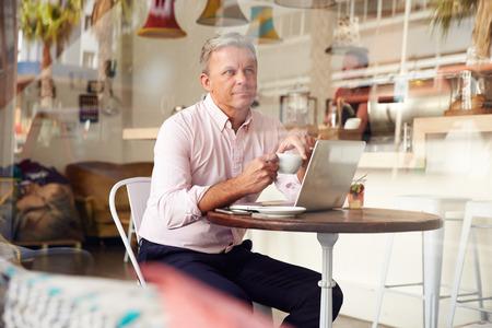 Mann mittleren Alters sitzt in einem Café Standard-Bild