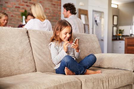 piedi nudi di bambine: Ragazza che gioca con la nuova tecnologia, mentre gli adulti intrattenere