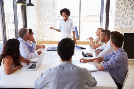 patron: Empresaria que presenta a sus colegas en una reunión Foto de archivo