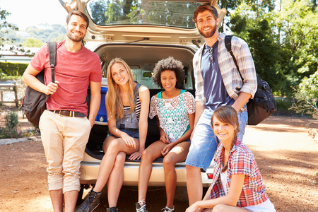 road trip: Group Of Friends On Trip Sitting In Trunk Of Car
