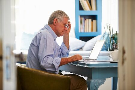 emails: Senior Man At Desk Working In Home Office With Laptop Stock Photo