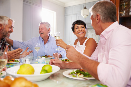 Group Of Mature Friends Enjoying Meal At Home Together 스톡 콘텐츠