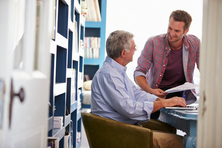 financial advice: Son Giving Senior Parent Financial Advice In Home Office