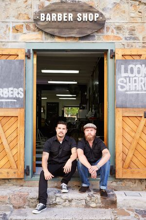 Portrait Of Two Hipster Barbers Standing Outside Shop photo