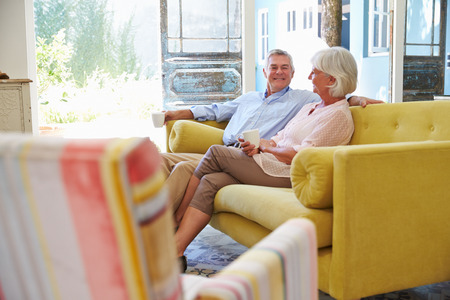 two people talking: Senior Couple At Home Relaxing In Lounge With Hot Drink Stock Photo