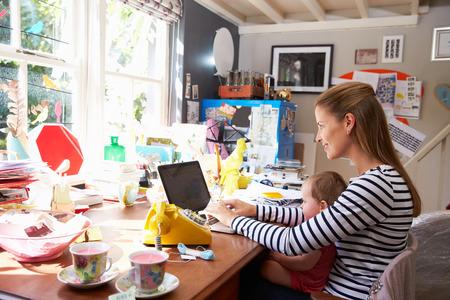 madre trabajando: Madre con la hija que ejecuta Small Business From Home Oficina Foto de archivo