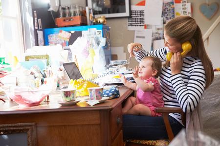 oficina desordenada: Madre con la hija que ejecuta Small Business From Home Oficina Foto de archivo