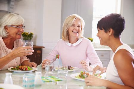 tomando agua: Grupo de Amigos femeninos maduros disfrutan de la comida en casa