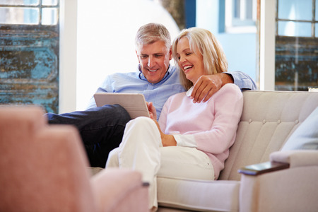 Mature Couple At Home In Lounge Using Digital Tablet Stock Photo