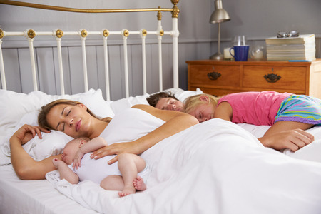 Family With Baby Lying Asleep In Bed Together