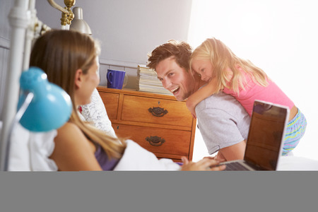 Family In Bedroom With Mother Using Laptop photo