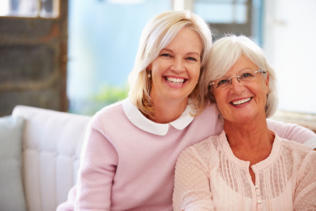 Senior Mother With Adult Daughter Relaxing On Sofa photo