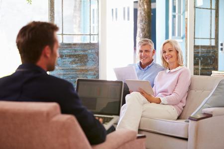Ouder paar thuis Ontmoeting Met Financieel Adviseur