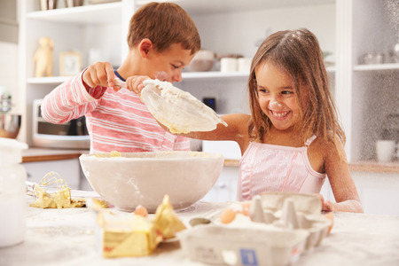 woman baking: Two children having fun baking in the kitchen Stock Photo