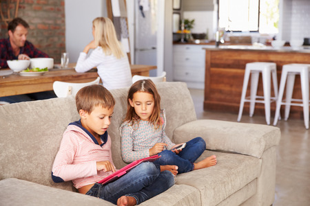 bare feet girl: Kids playing with new technology while adults entertain Stock Photo
