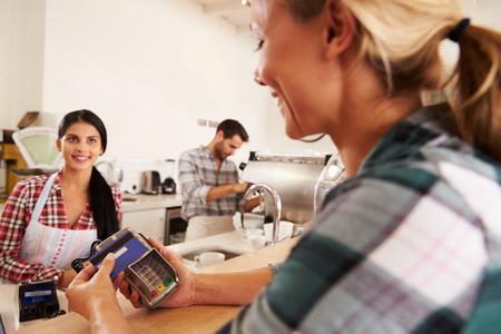cafe internet: Mujer que paga con tarjeta de cr�dito en un caf� Foto de archivo