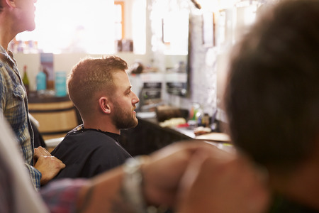 hair cutting: Male Barber Giving Client Haircut In Shop
