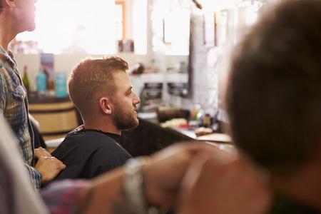 horizontal haircut: Male Barber Giving Client Haircut In Shop