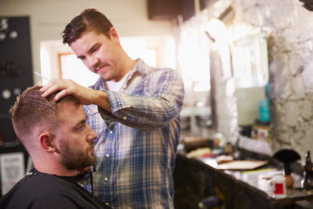 male grooming: Male Barber Giving Client Haircut In Shop