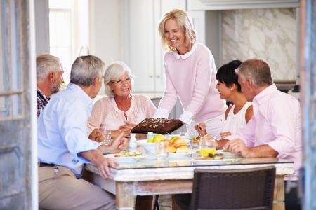 女性の家庭での食事を楽しんでいる友人のグループにケーキを提供