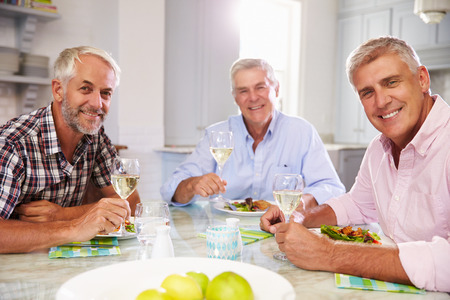 mature male: Portrait Of Mature Male Friends Enjoying Meal At Home
