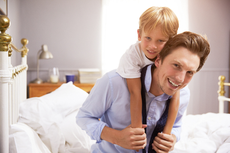 Son Hugging Father As He Gets Dressed For Work Stock Photo