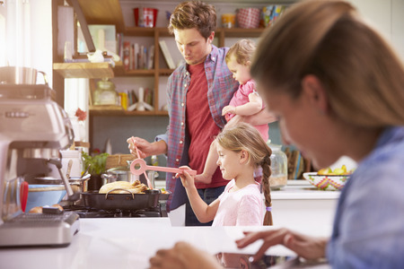 Father Cooks Family Meal Whilst Mother Uses Digital Tablet Banco de Imagens
