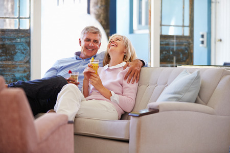 retirement happy man: Mature Couple At Home Relaxing In Lounge With Cold Drinks