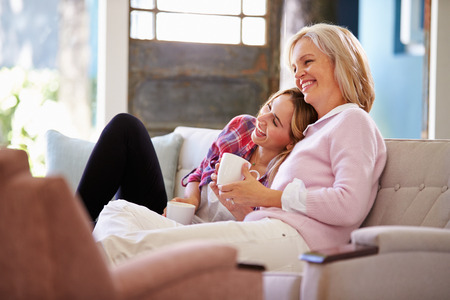 Mature Mother With Adult Daughter Watching TV At Home photo