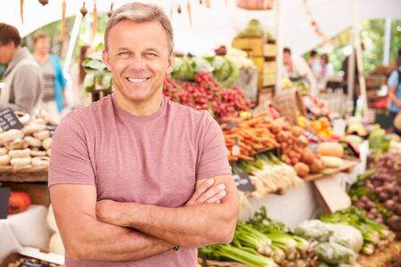 local: Male Stall Holder At Farmers Fresh Food Market Stock Photo