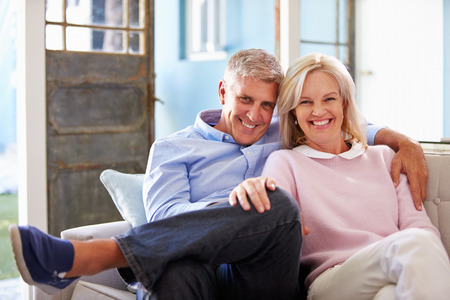 couple on couch: Portrait Of Smiling Mature Couple Sitting On Sofa At Home