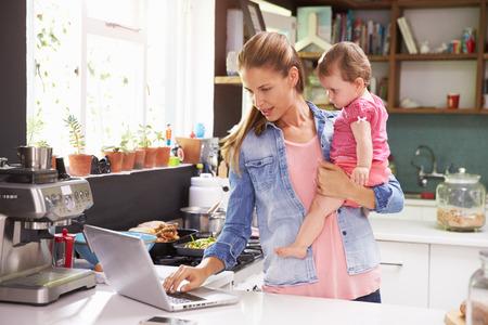 キッチンでラップトップを使用して若い娘を持つ母